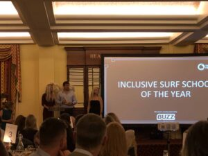 Buzz sponsors charity award for Inclusive Surf School of the Year at The Wave Project event.